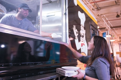patron getting order from food truck